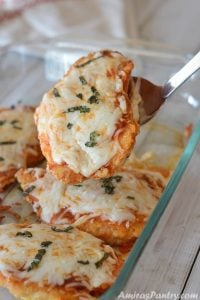Low carb chicken parmesan casserole being scooped out of a glass dish