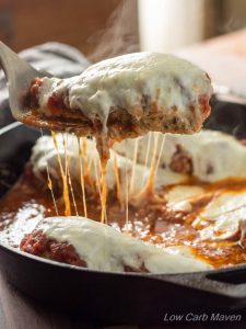 low carb chicken parmesan in a skillet with cheese stringing from one breast