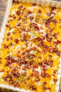 Smothered pork chops with bacon and cheese in a gold trimmed dish