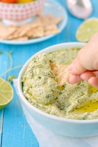 spinach avocado dip in a bowl beside lime wedges
