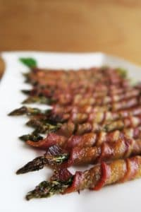bacon wrapped asparagus lined up on a plate