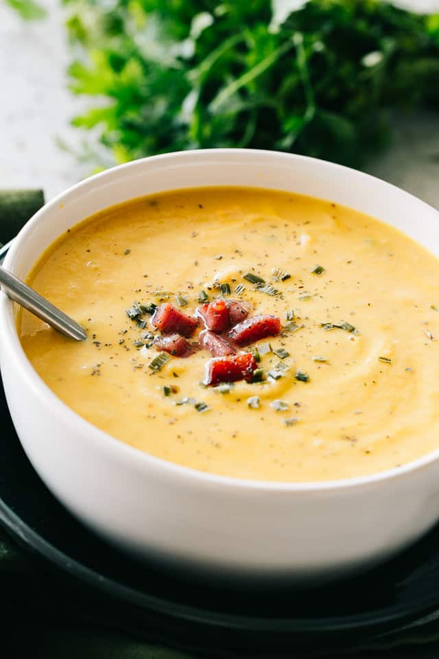 bowl of cauliflower cheese soup topped with bacon and spices
