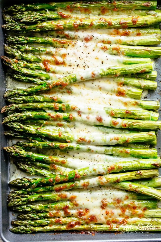 cheesy garlic roasted asparagus lined up on a baking sheet
