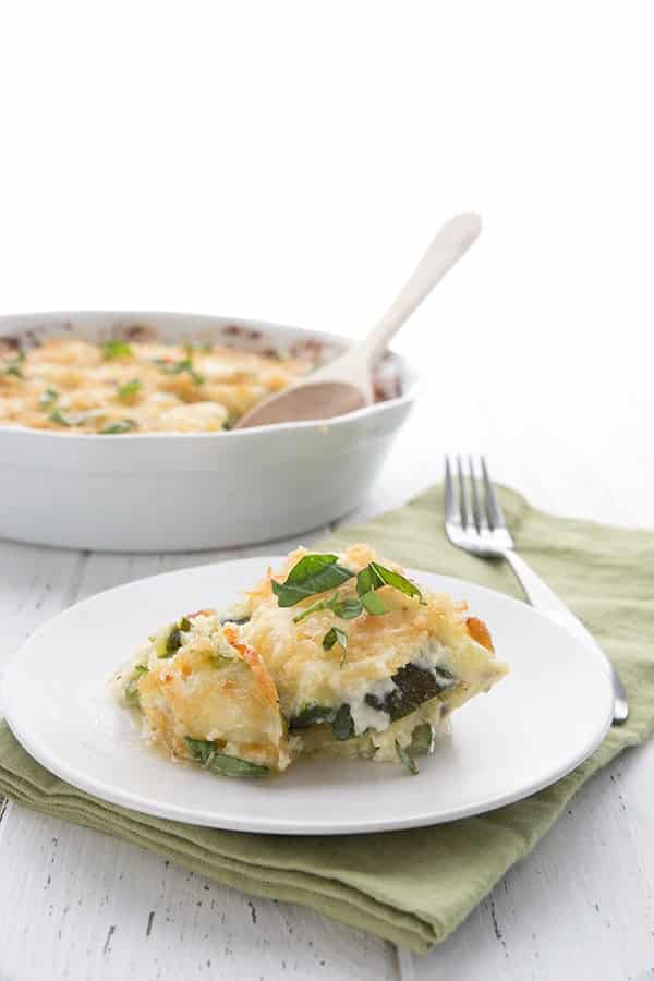 one serving of cheesy zucchini casserole with dish in the background