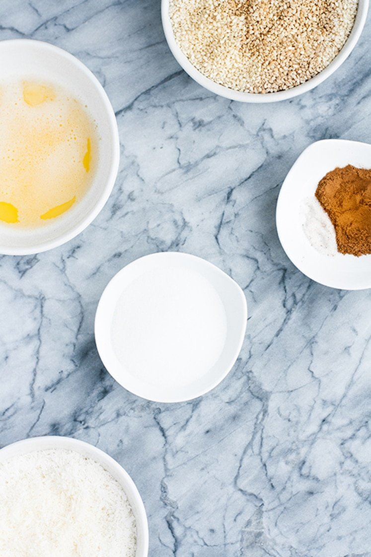 nut free keto cheesecake crust ingredients assembled in small bowls atop marble kitchen counter