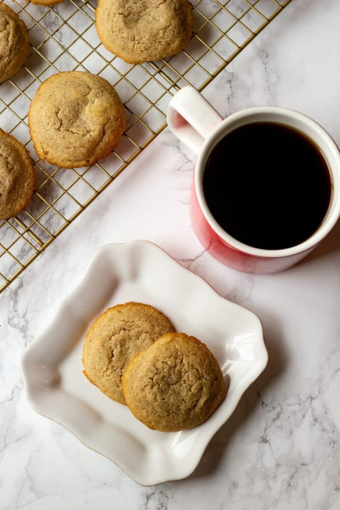 snickerdoodles on a plate and cooling tray with a cup of coffee