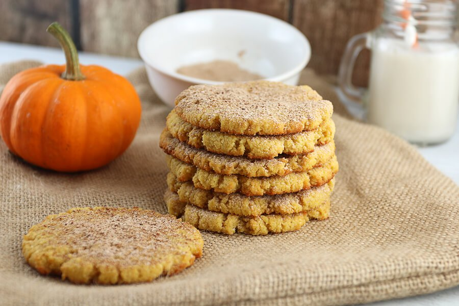 stack of keto pumpkin snickerdoodle cookies on burlap with a pumpkin aside