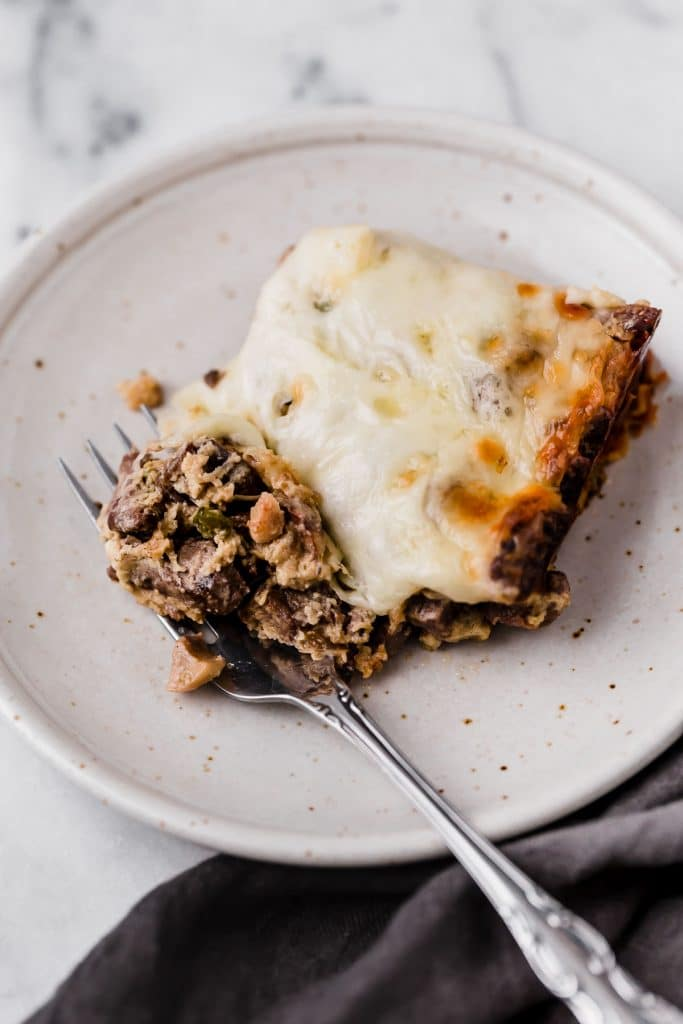 a serving of low carb philly cheesesteak casserole on a plate eaten with a fork