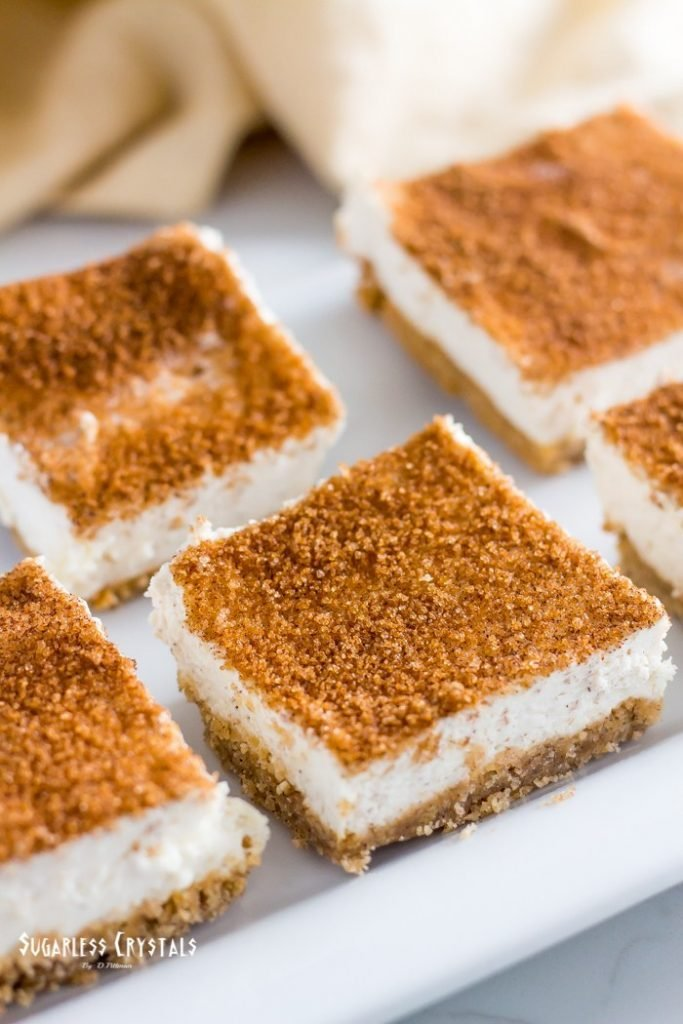 snickerdoodle cheesecake bars sliced and topped with cinnamon