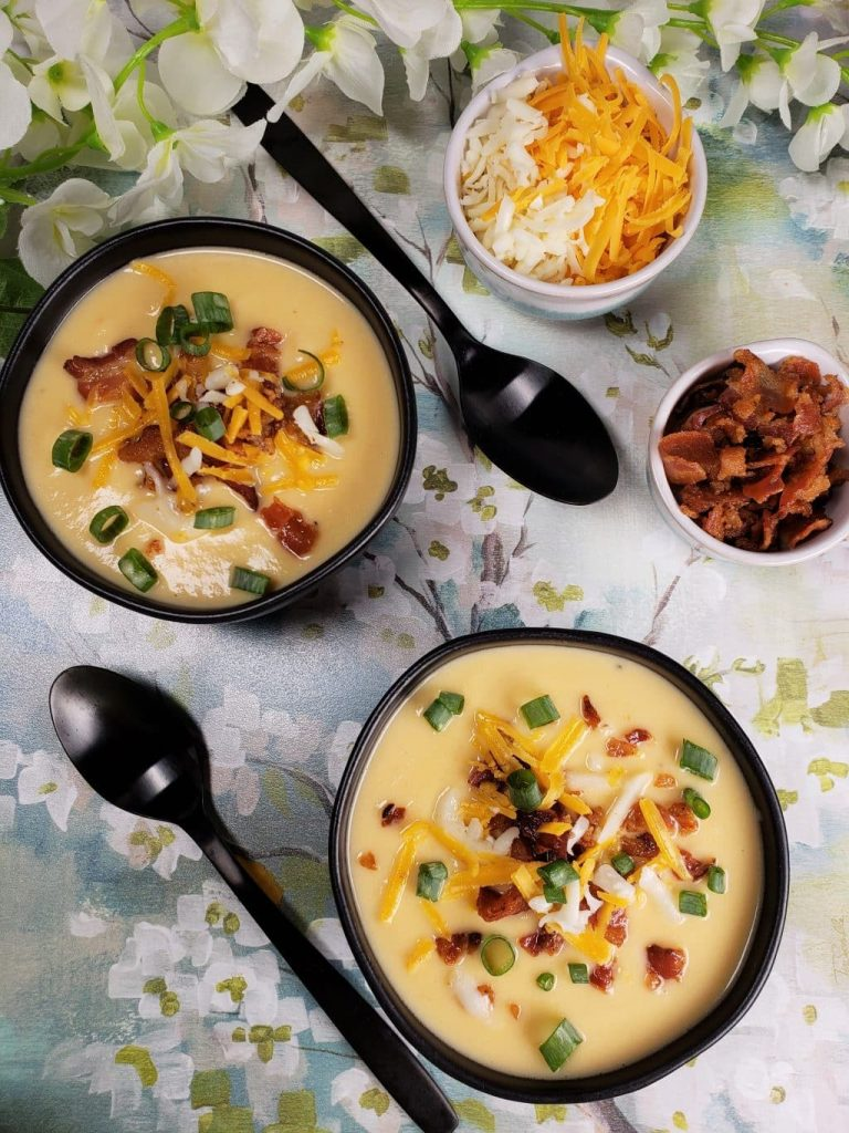two bowls of low carb cheesy cauliflower soup with spoons and toppings surrounding