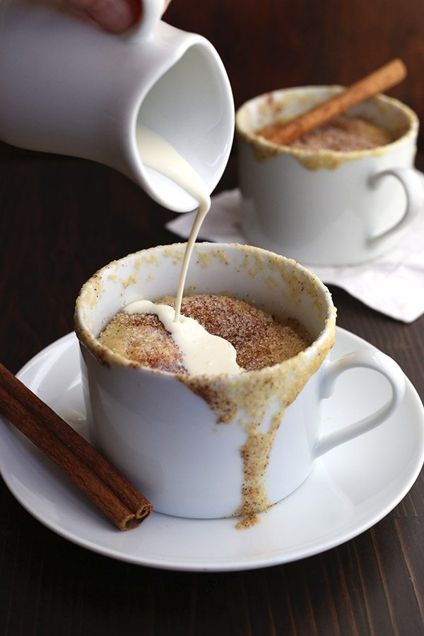 Snickerdoodle mug cake with cream being drizzled on top