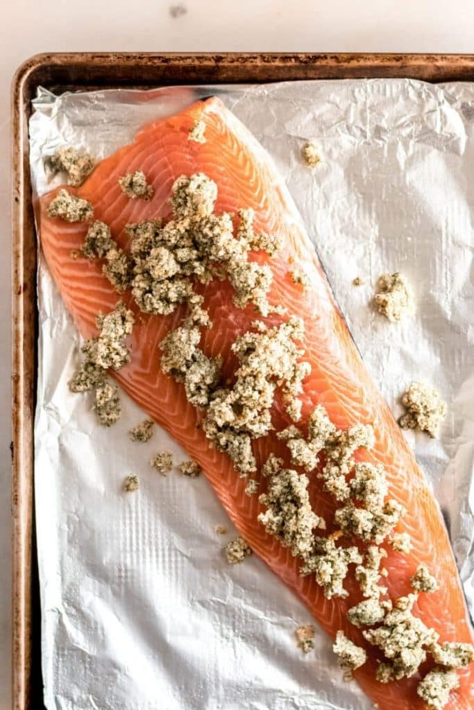 raw deboned salmon fillet topped with parmesan dill mixture