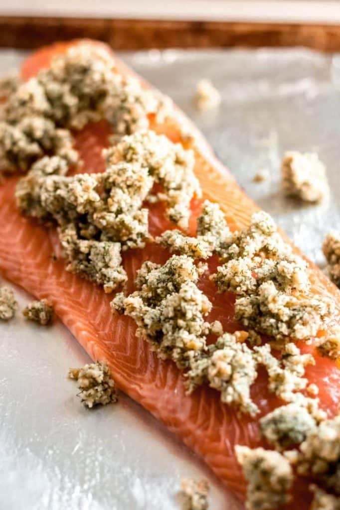 raw deboned salmon fillet topped with parmesan dill mixture close up