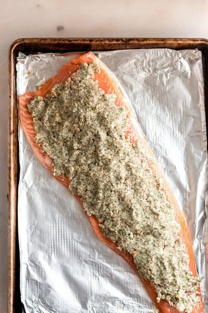 raw deboned salmon fillet topped with parmesan dill spread evenly on the fish
