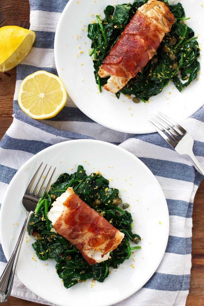 two plates of prosciutto wrapped cod atop a bed of kale