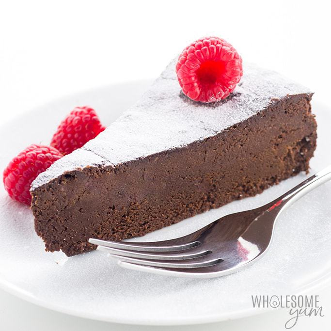 gluten-free sugar-free flourless chocolate cake topped with powdered sweetener and raspberries