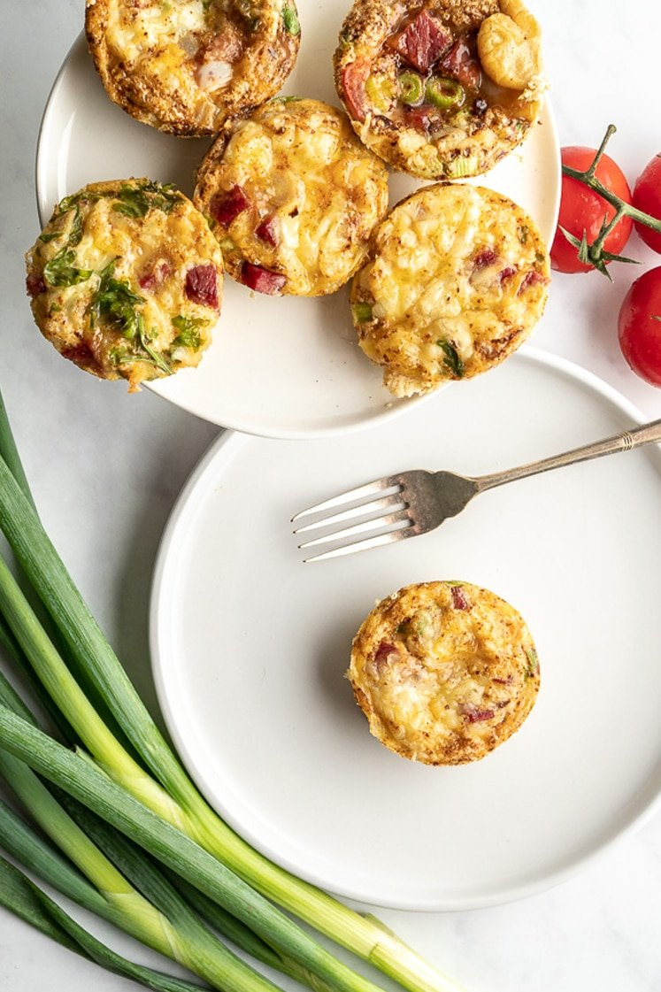baked keto breakfast muffins on a plate with a fork, spring onion stalks and whole fresh tomatoes