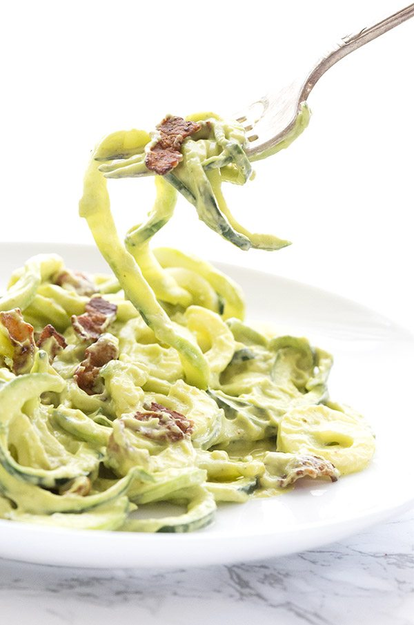 creamy avocado & bacon zoodles being swirled on a fork