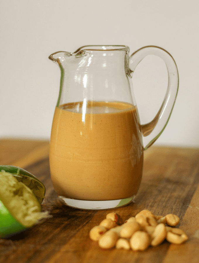 creamy thai peanut dressing in a glass pouring container