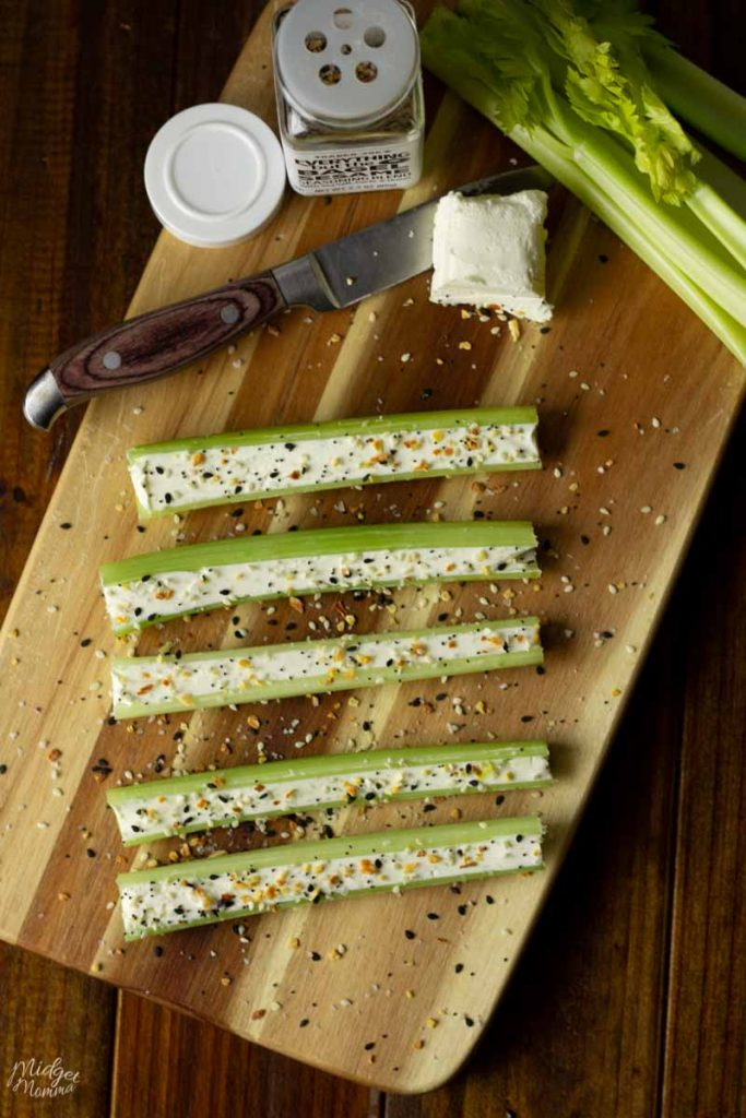 Everything bagel celery and its ingredients on a cutting board