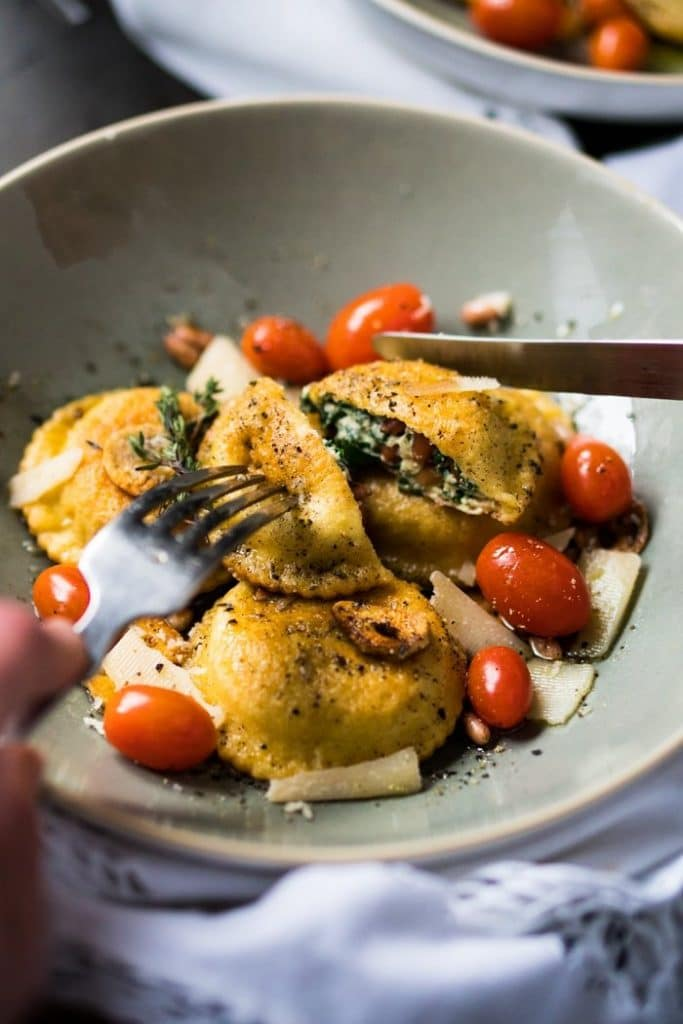 spinach and ricotta fried ravioli in a gray bowl with one being cut in half