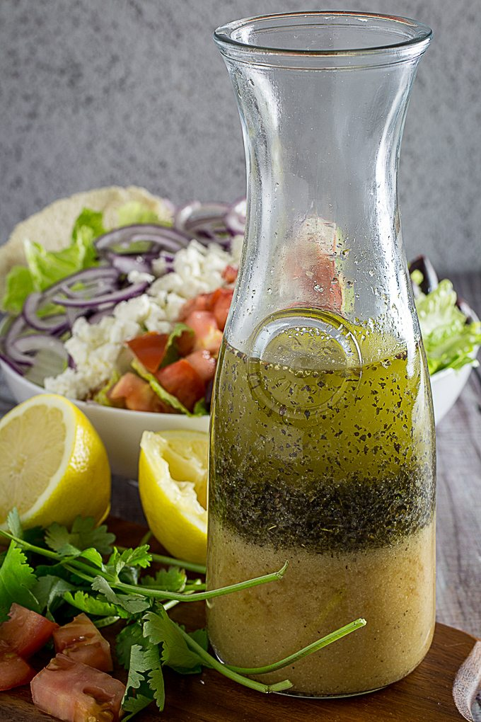 greek salad dressing with greek salad in the background