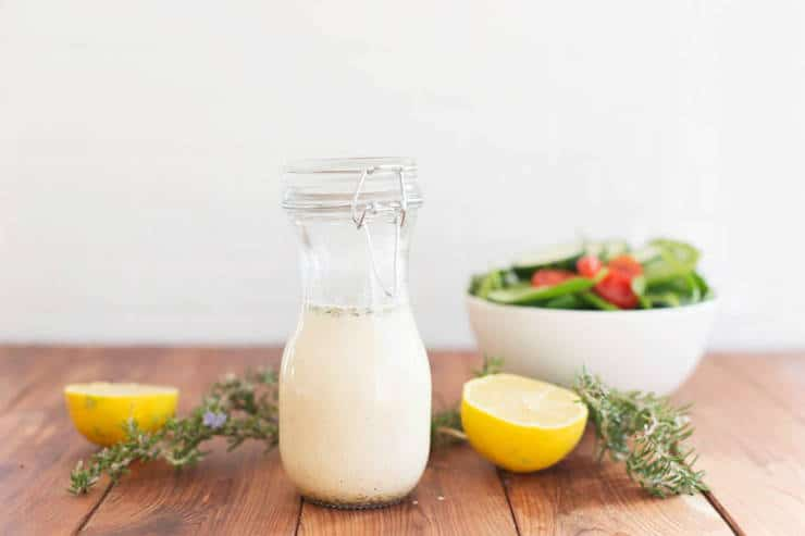 creamy lemon vinaigrette with salad and lemons in the background