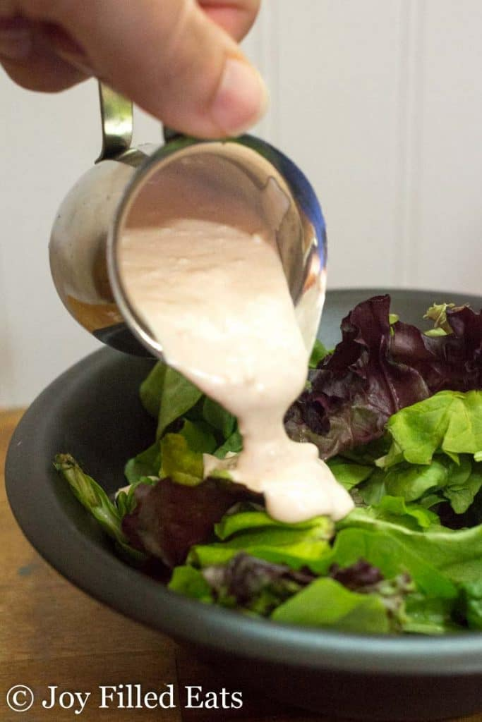 creamy garlic salad dressing being poured onto greens