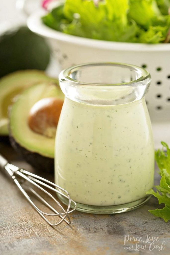 keto creamy avocado ranch dressing in a glass container with a whisk