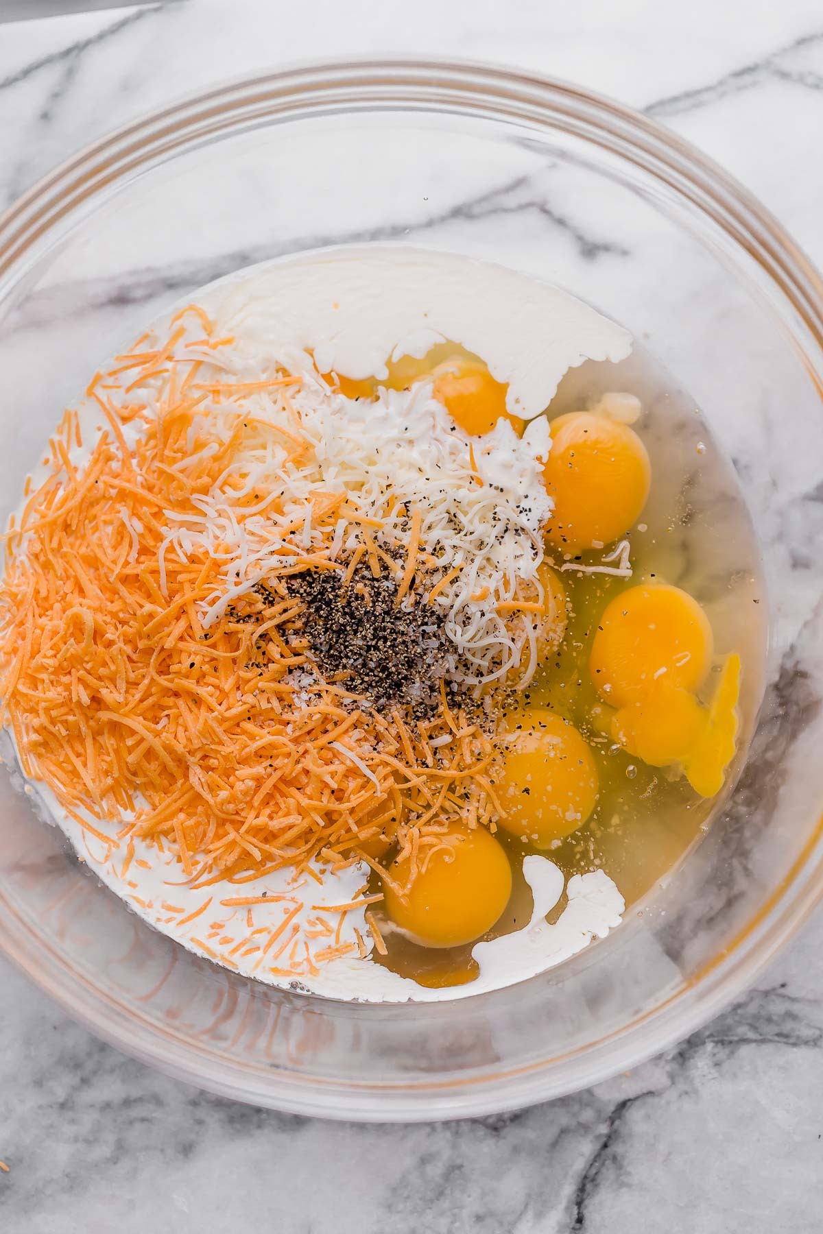 eggs, shredded cheddar, shredded mozzarella, heavy cream, salt, pepper on a glass mixing bowl