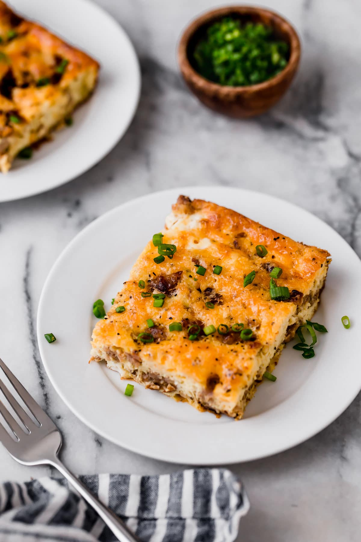 2 servings of Low Carb Sausage Breakfast Casserole on a small plate atop a marble kitchen counter beside a fork