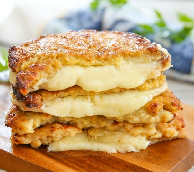 stack of cauliflower crusted grilled cheese sandwiches with cheese oozing out