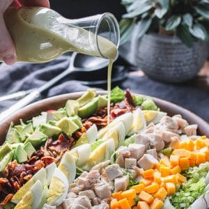 cobb salad dressing being poured on a salad
