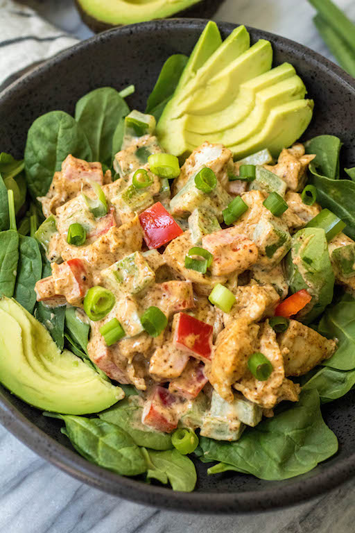 taco chicken salad on a bed of spinach with sliced avocado