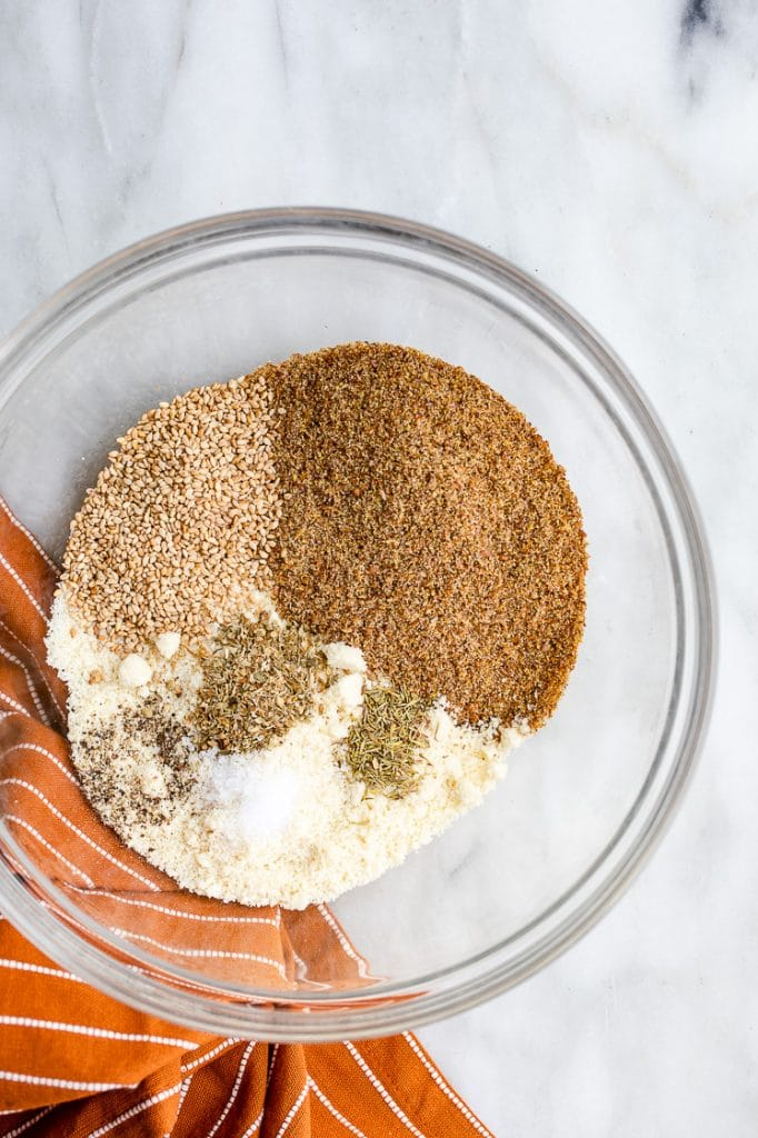 keto cracker dry ingredients in a glass mixing bowl atop a marble kitchen counter