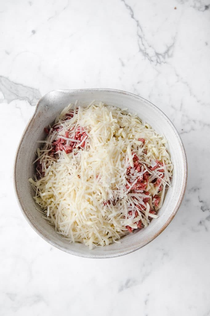 meat and cheese in a bowl atop a marble kitchen counter