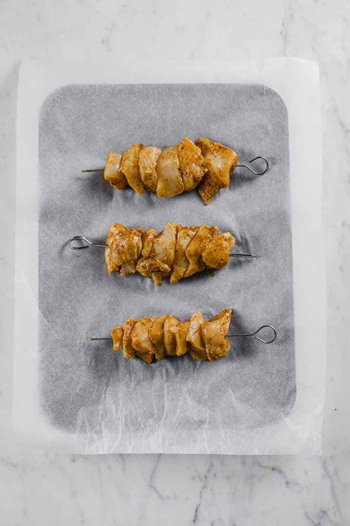 3 skewers of chicken kebabs placed on a baking tray lined with parchment paper