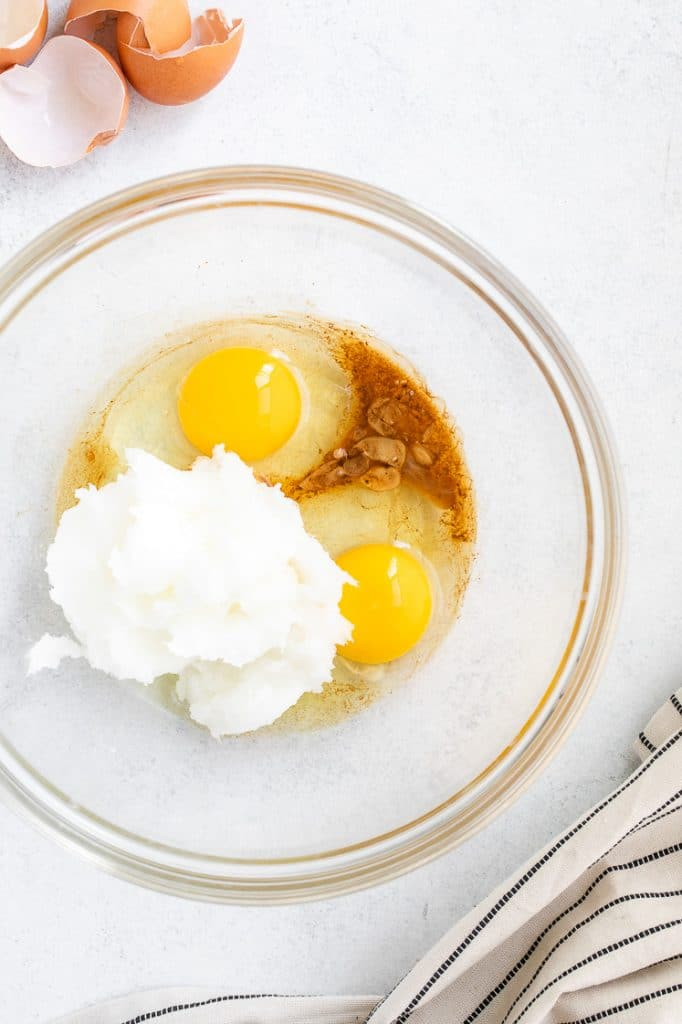 eggs, monk fruit sweetener, and coconut butter in a glass mixing bowl