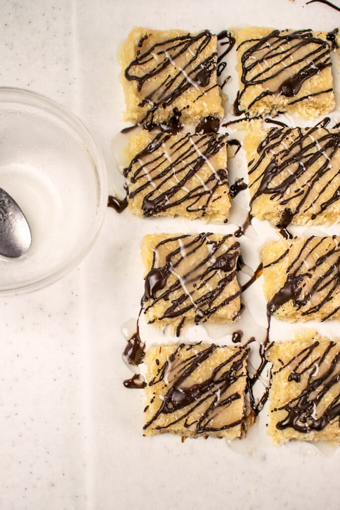 coconut bars drizzled with melted dark chocolate and vanilla glaze on a baking sheet lined with parchment paper