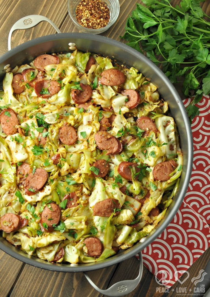 fried cabbage with kielbasa in a skillet with parsley and red pepper beside it