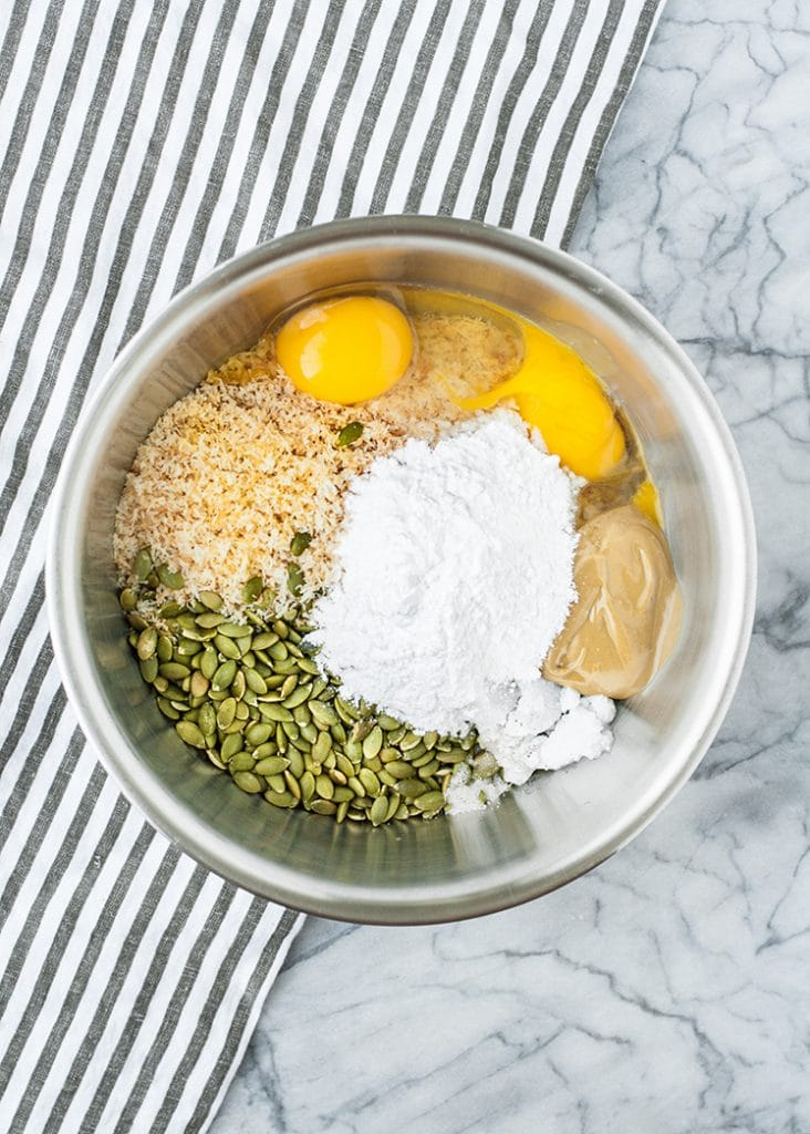 toasted pumpkin seeds, shredded coconut, eggs, SunButter, coconut oil, salt and monkfruit sweetener in a large stainless steel mixing bowl atop a marble kitchen counter