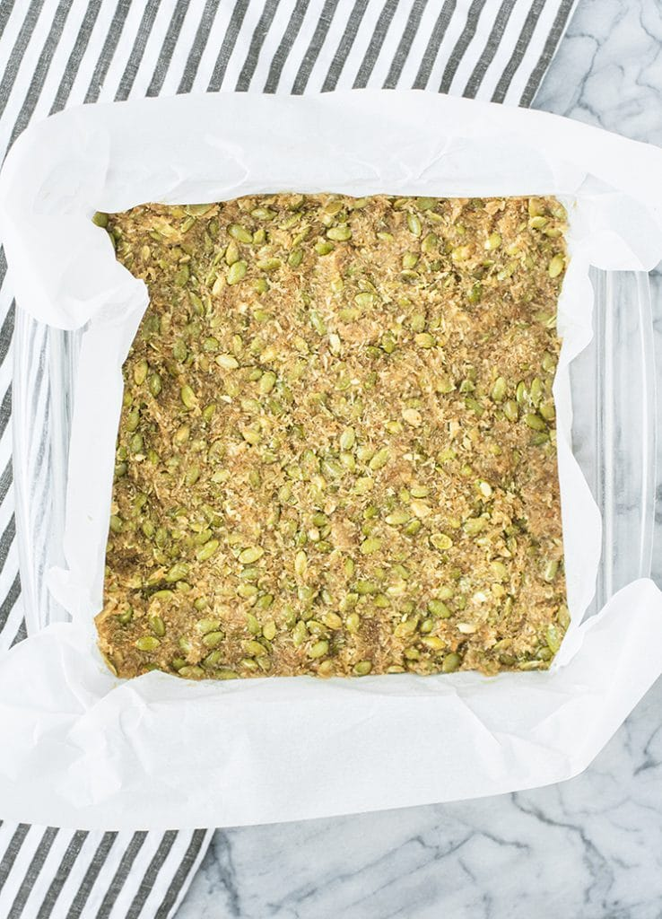low carb nut free granola bar mixture spread onto a baking pan lined with parchment paper