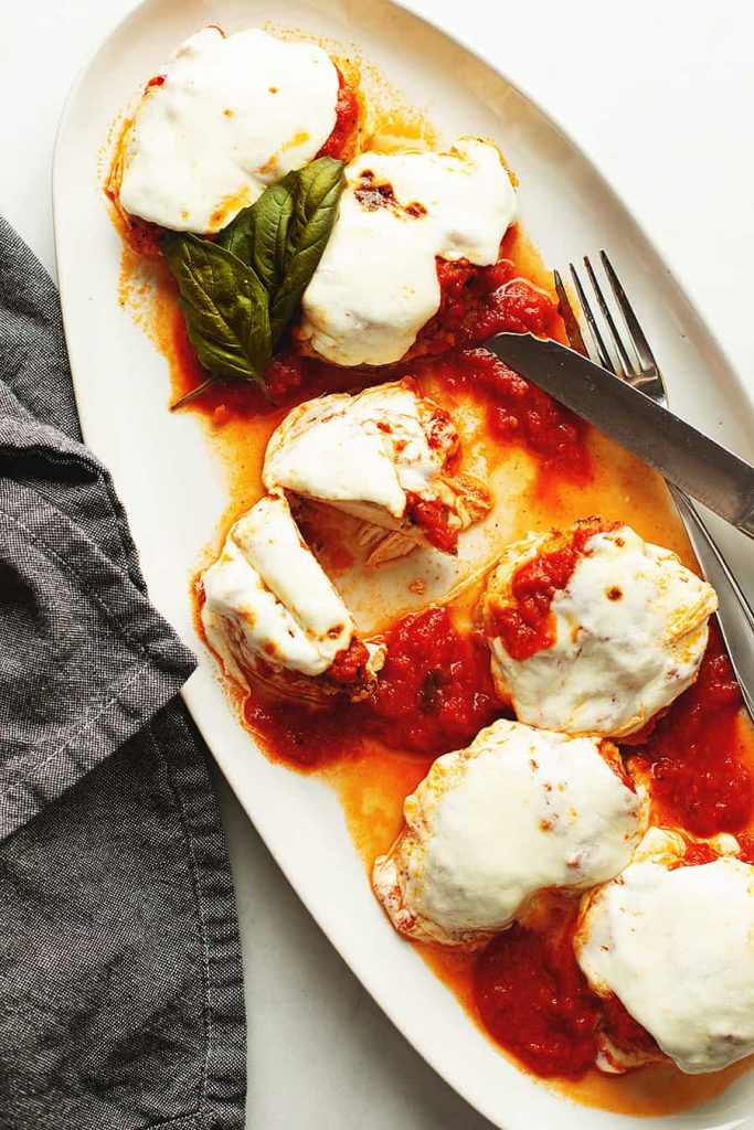 keto chicken parmesan pieces spread on a white serving dish with utensils and basil
