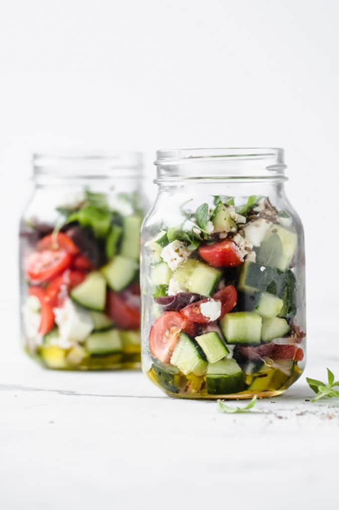 featured recipe image - 2 jars of low carb greek salad atop a marble kitchen counter