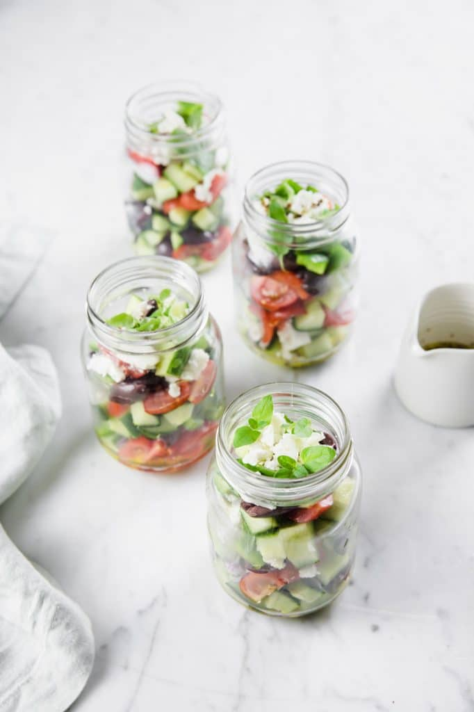 4 Low Carb Greek Salad Meal Prep Jars atop a marble kitchen counter beside some salad dressing
