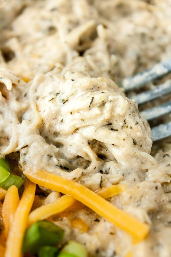 close-up shot of Keto Creamy Ranch Chicken Freezer Meal garnished with cheddar and green onions being scooped by a fork