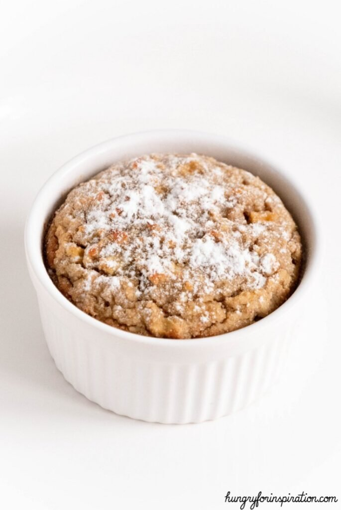 one Cinnamon Apple Pie Keto Mug Cake atop a marble kitchen counter