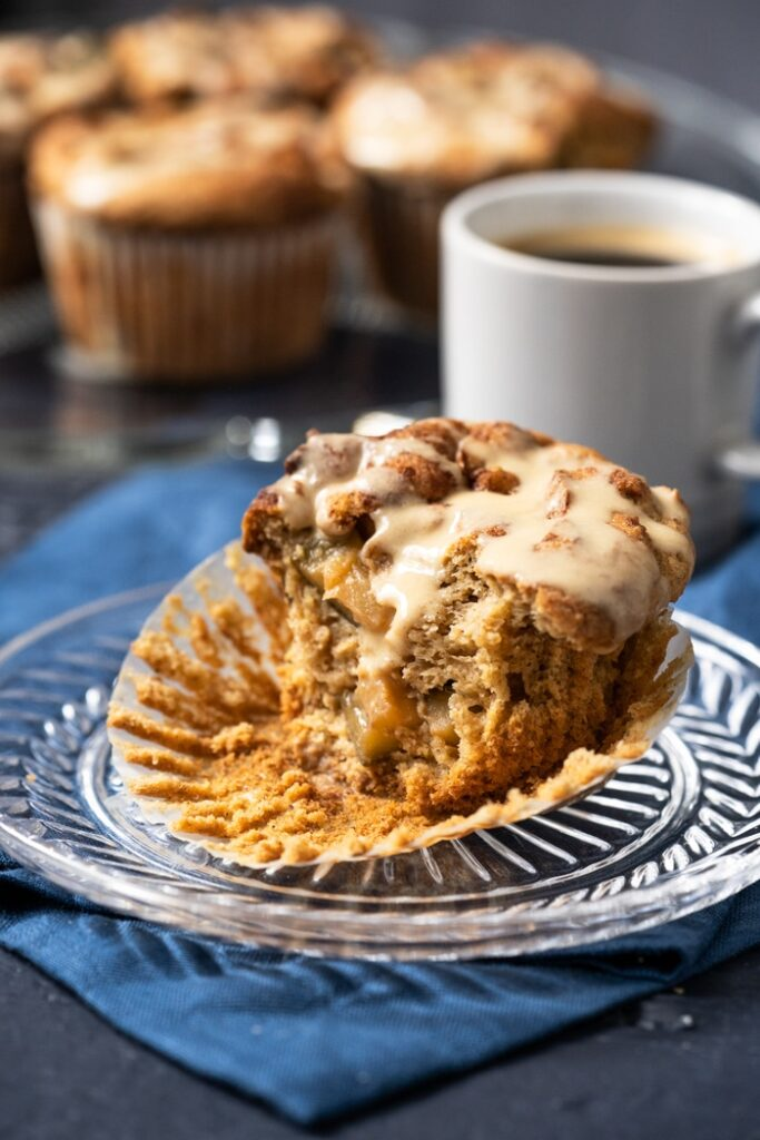 one Legit Low Carb & Keto Apple Muffins with a bite missing and a cup of coffee in the background
