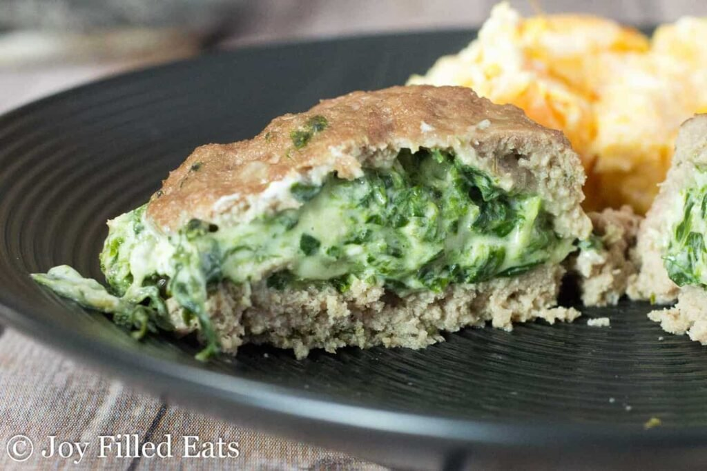 1 serving of Stuffed Turkey Burgers with Spinach & 3 Cheeses on a black plate with garnish