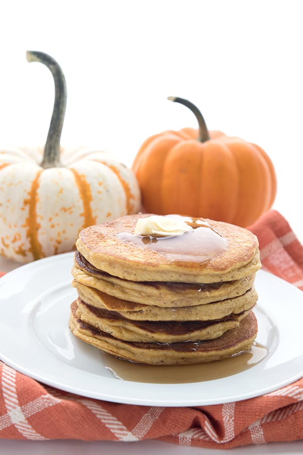 a stack of keto pumpkin pancakes with 2 decorative pumpkins in the background